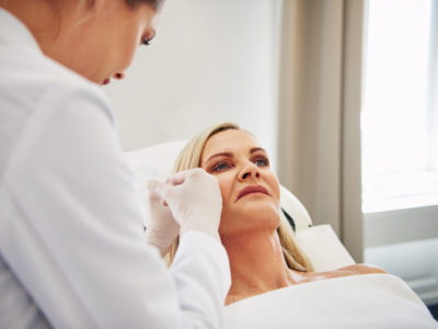 Female doctor administering botox injections to the face of a mature woman lying on a table in a beauty clinic